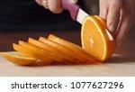 Hand Slicing Orange On Wooden...