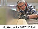 man working in wood industry...   Shutterstock . vector #1077699560