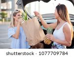 two happy young women loading... | Shutterstock . vector #1077709784