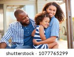 black family embracing outdoors ... | Shutterstock . vector #1077765299