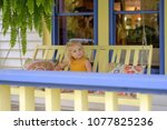 little girl sitting on a porch... | Shutterstock . vector #1077825236