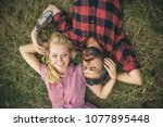 Young couple in love. Two people, blond girl and bearded man, lying on green grass. Girlfriend and boyfriend playing with each others hair.