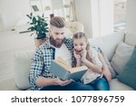 Small photo of WOW! Stylish handsome father with red hair sitting with surprised daughter on couch indoor in modern house reading funny comic story enjoying interesting poem education concept