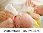 mother of twin babies feeding... | Shutterstock . vector #1077910376