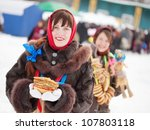 Smiling girls in russian traditional clothes with pancake during  Shrovetide - stock photo