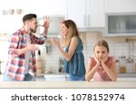 Small photo of Little unhappy girl sitting at table while parents arguing on kitchen
