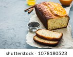 Sliced orange poppy seeds pound cake on light blue concrete background. Selective focus, space for text.  - stock photo