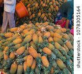 Small photo of Stacks of pineapples for sale in a city center market in Mysore, India