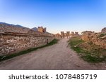 Small photo of View on stony path leading between wall with tower and dilapidated wall of ancient fortress, all made of coarse stone, and towers in distance under clean blue sky just after sunset in Crimea