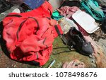Small photo of dirty red sweatshirt and a black shoe with tatters in the homeless shelter