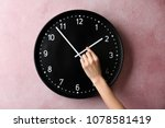 Small photo of Woman changing time on big wall clock