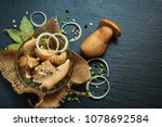 Small photo of Marinated white mushrooms, porcini with spices, garlic and onions on black slate board, plate or tray. Vegetarian menu.