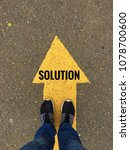 Small photo of Solution text on yellow arrow on asphalt ground, feet and shoes on floor, personal perspective footsie concept
