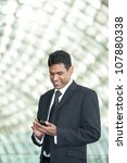 Portrait of handsome Indian business man using cell phone. - stock photo