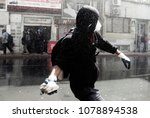 a masked protester throws... | Shutterstock . vector #1078894538