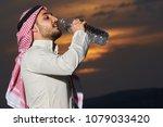 muslim drinking water at sunset | Shutterstock . vector #1079033420