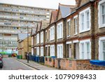 Traditional English terraced houses with huge council block Aylesbury Estate in the background in south east London