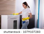 smiling young woman cleaning... | Shutterstock . vector #1079107283