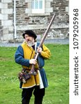 Small photo of Falmouth, Cornwall, UK - April 12 2018: Historical military re-enactor dressed in bleu and yellow Tudor clothes with leather equipment demonstrating a working musket