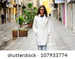 Portrait of a beautiful woman with eyesglasses walking in urban background - stock photo