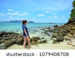 Small photo of Women's blue sweater girl Raven, omission of fashion are standing by the sea with ships sailing through the fit. During the summer, Krabi Province of Thailand.