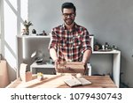 Small photo of Gift for you! Handsome young man giving a gift box and looking at camera with smile while standing in the creative working space