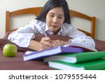 Small photo of Young woman concentrate reading, writing book. education assessment concept. Student studying college exam, homework at university. concentration on admissions.