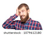 Small photo of A young bearded man in a plaid shirt is experiencing an annoying mistake or oversight. Emotional portrait on a white background.