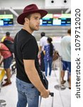 Small photo of Man in a crimson hat with a travel bag stands in the line in the airport. He wears a black T-shirt, shoulder pouch and blue jeans. Closeup. Vertical.