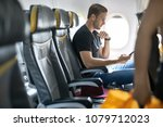 cute man sits in the airplane... | Shutterstock . vector #1079712023