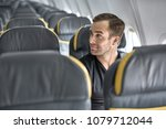 joyful man sits in the airplane ... | Shutterstock . vector #1079712044