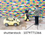 happy child washes yellow toy... | Shutterstock . vector #1079771366