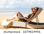 Small photo of Summer lifestyle fashion portrait of young stunning woman drinking young coconut on the beach of the tropical island. Enjoying life on the beach chaise. Wearing stylish sunglasses, bikini. Sunbathing.
