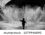 silhouette of happy a child playing in a water fountain in the light of the setting sun. The gush of water of a fountain in city park on hot summer day.  abstract black and white image.