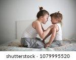 sister's girls play and hug ... | Shutterstock . vector #1079995520