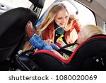mom puts the child in the car... | Shutterstock . vector #1080020069