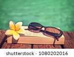 book and sunglasses  blue water ... | Shutterstock . vector #1080202016