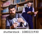 Small photo of Man in oldfashioned suit holds money. Journalist got reward for article from publisher. Writer with strict face with typewriter in library with books on background, defocused. Yellow press concept.