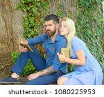 Small photo of Girl with pensive face listen bearded man reading poems. Romantic couple holds old book with poems about love. Romantic vintage date concept. Couple in love hugs outdoor, nature background, defocused.