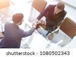 handshake across the table of... | Shutterstock . vector #1080502343