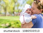 cute baby in her mothers arms... | Shutterstock . vector #1080533513