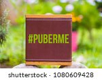 Small photo of PuberMe hashtag on a brown leather texture, social media campaign