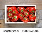 ripe tomatoes in wooden box... | Shutterstock . vector #1080660308