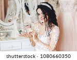 cute bride holding a perfume at ... | Shutterstock . vector #1080660350