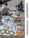 Small photo of ASWAN, EGYPT - MARCH 18, 2010 : Souvenir salesmen set up a display of various necklaces on a cloth sheet at the ferry port in Aswan, Egypt.