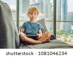 boy uses a tablet at home on... | Shutterstock . vector #1081046234