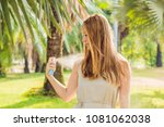woman spraying insect repellent ... | Shutterstock . vector #1081062038