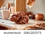 Large piece of red clay closeup on worktop at the potter workshop, close-up, shallow depth of field