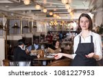 smiling young waitress warmly... | Shutterstock . vector #1081227953