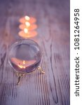 Small photo of mystical still life with candles and glass transparent ball (sphere). mysterious, magical composition. dark tone, toning, soft selective focus